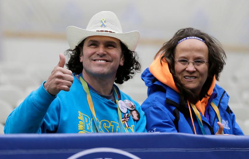 . Carlos Arredondo, a 2013 Boston Marathon first-responder, and his wife, Melida, sit in the grandstand near the Boston Marathon finish line Monday, April 20, 2015, in Boston. (AP Photo/Elise Amendola)