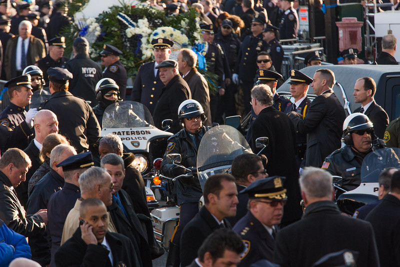 . Police officers gather outside the funeral of slain New York Police Department (NYPD) officer Rafael Ramos at the Christ Tabernacle Church on December 27, 2014 in the Glenwood section of the Queens borough of New York City. Ramos was shot, along with Police Officer Wenjian Liu while sitting in their patrol car in an ambush attack in Brooklyn on December 20. Thousands of fellow officers, family, friends and Vice President Joseph Biden arrived at the church for the funeral.  (Photo by Kevin Hagen/Getty Images)