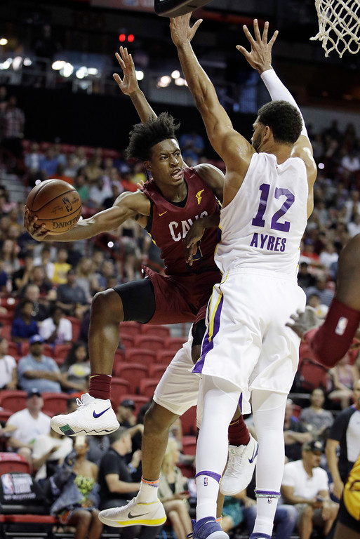 . Cleveland Cavaliers\' Collin Sexton passes around Los Angeles Lakers\' Jeff Ayres during the first half of an NBA summer league basketball game Monday, July 16, 2018, in Las Vegas. (AP Photo/John Locher)