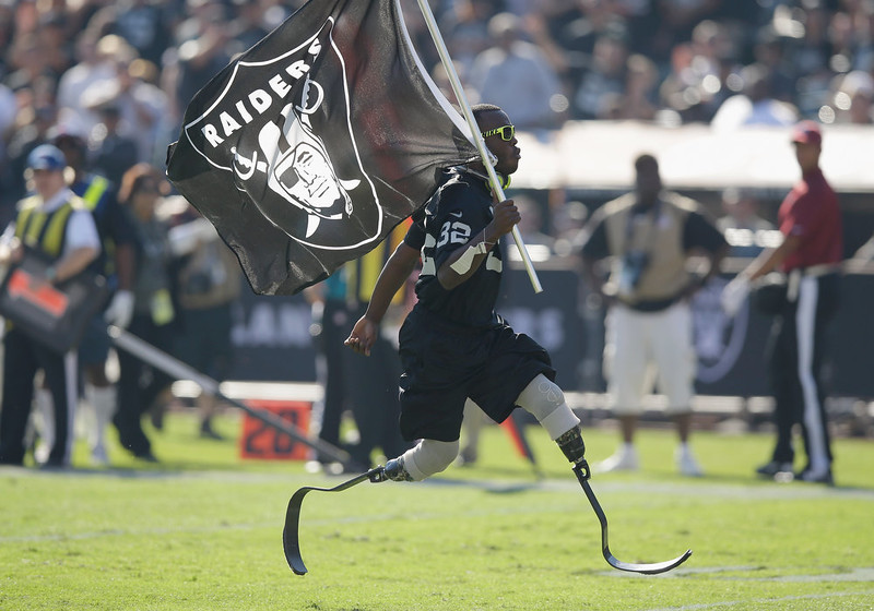 . Olympic sprinter Blake Leeper carries the Oakland Raiders flag in a break in play against the Denver Broncos at O.co Coliseum on November 9, 2014 in Oakland, California.  (Photo by Ezra Shaw/Getty Images)