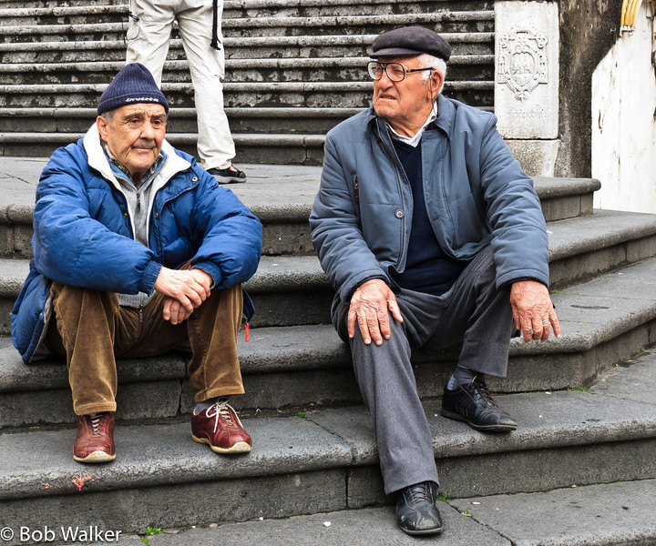 Two locals sitting on steps near the Duomo