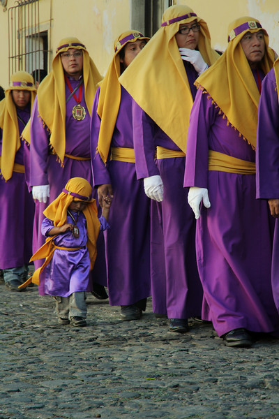A young boy holds hands with an adult as they parade through the streets of Antigua, Guatemala in celebration of Lent on February 17, 2013. Photo by Scott Umstattd