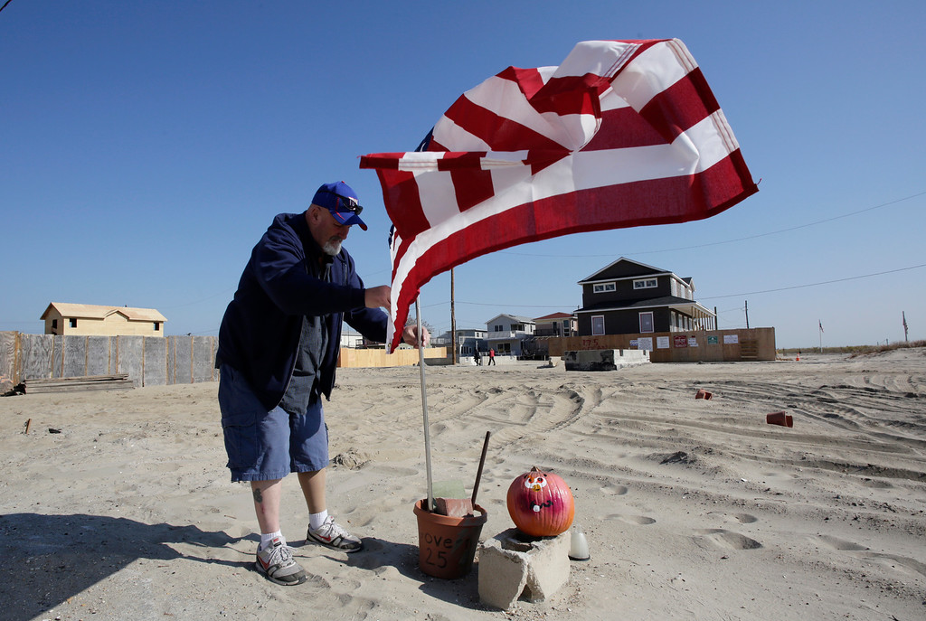 . Tom Hammill places an American flag at a building site in the Breezy Point neighborhood in the Queens borough of New York, Tuesday, Oct. 29, 2013, a year after Superstorm Sandy struck. A firestorm spread across the beachfront neighborhood during the storm, burning more than 100 homes, including Hammill\'s. Behind him are homes that are being rebuilt. (AP Photo/Mark Lennihan)