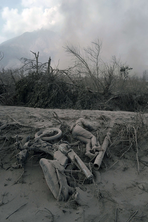 . The body of a victim is covered with hot volcanic ash at a village in Karo district following eruptions of Mount Sinabung volcano, seen in the background, located in Indonesia\'s Sumatra island on February 1, 2014. AFP PHOTO / SUTANTA ADITYA/AFP/Getty Images
