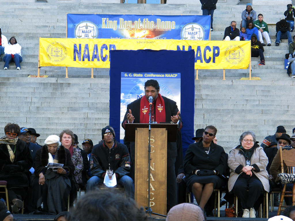. North Carolina NAACP President William Barber talks about fighting for social justice at the King Day rally on Monday, Jan. 20, 2014, in Columbia, S.C. Barber told the crowd of a few thousand people that what conservatives leaders have done to the country is mighty low, but he thinks they are ready to find higher ground. (AP Photo/Jeffrey Collins)