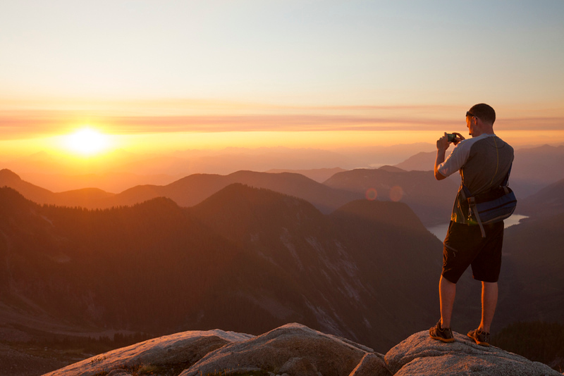 A hiker takes a picture of the sunset from a mountain ridge.