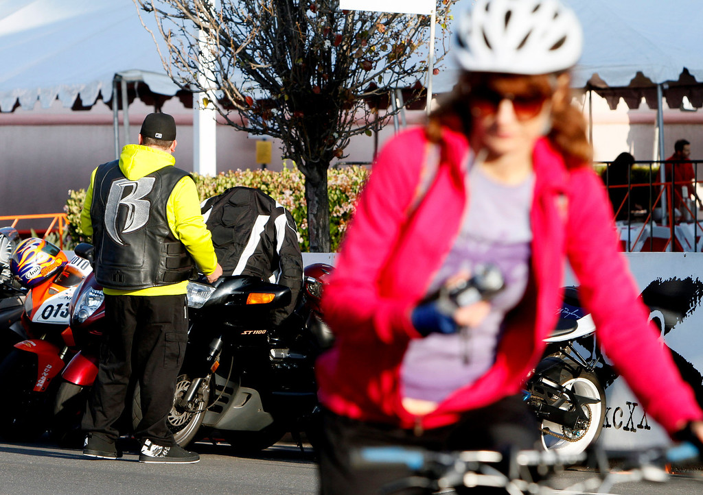 . A member of the Ruff Riders Motorcycle Club, left, is seen as a female cyclist warms up for the R.U.F.F Ride during the public race portion of the Redlands Bicycle Classic on Saturday, April 5, 2014 in Redlands, Ca. (Photo by Micah Escamilla for the Redlands Daily Facts)