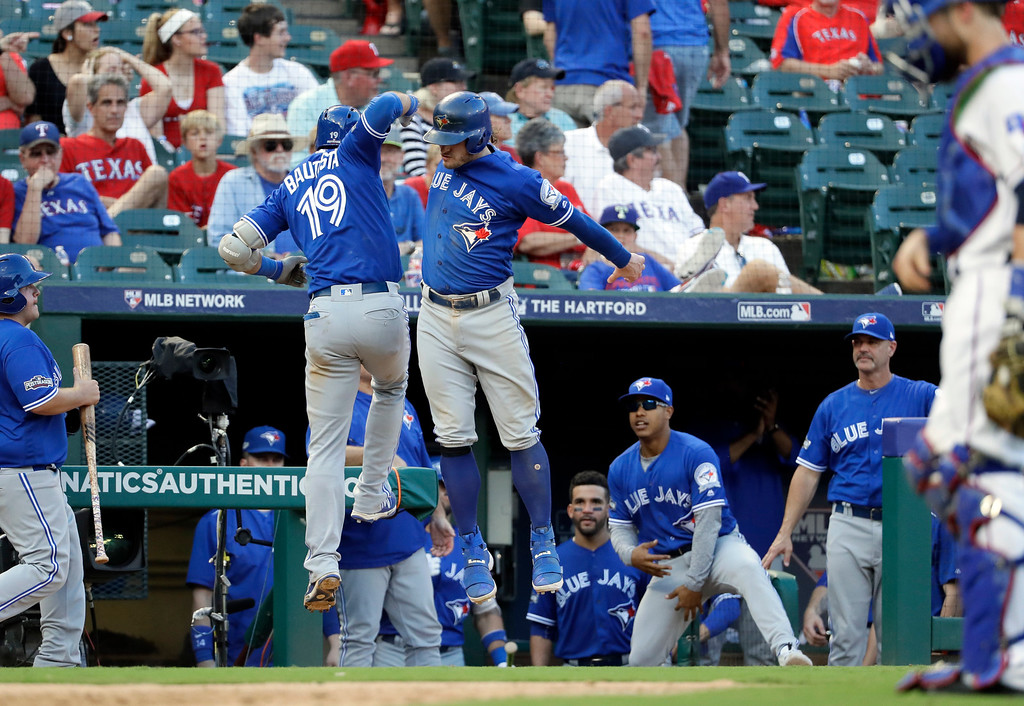 . Toronto Blue Jays\' Jose Bautista (19) and Josh Donaldson, right, celebrate Bautista\'s three-run home run against the Texas Rangers in the ninth inning of Game 1 of baseball\'s American League Division Series, Thursday, Oct. 6, 2016, in Arlington, Texas. The shot scored Donaldson and Edwin Encarnacion. (AP Photo/David J. Phillip)