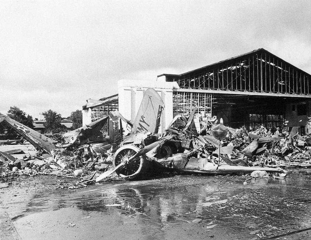 . In this photo provided by the Department of Defense, U.S. aircraft destroyed as a result of the Japanese bombing on Pearl Harbor is shown, Dec. 7, 1941. Heap of demolished hanger in background Army amphibian in foreground. (AP Photo/DOD)