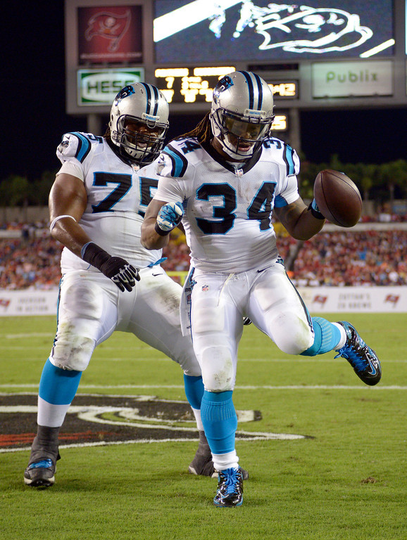 . Carolina Panthers running back DeAngelo Williams (34) celebrates his 12-yard touchdown run against the Tampa Bay Buccaneers with teammate Chris Scott (75) during the first half of an NFL football game in Tampa, Fla., Thursday, Oct. 24, 2013. (AP Photo/Phelan M. Ebenhack)