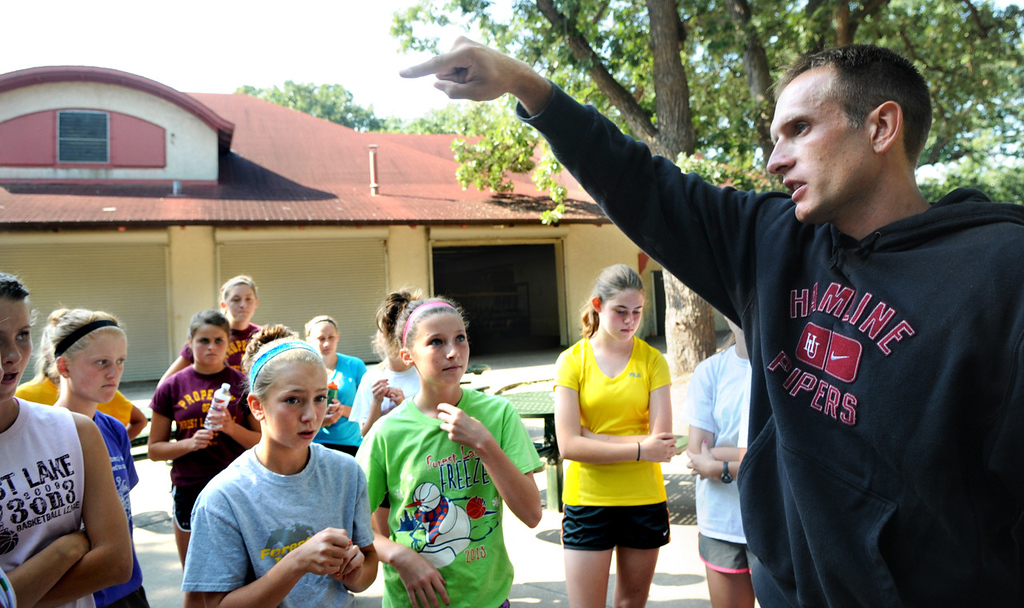 . Forest Lake girls cross country coach Eric Kaluza, right, tells the team which group they will run in and how far they will run at the start of a team practice at Minnehaha Falls Park. (Pioneer Press: Jean Pieri)