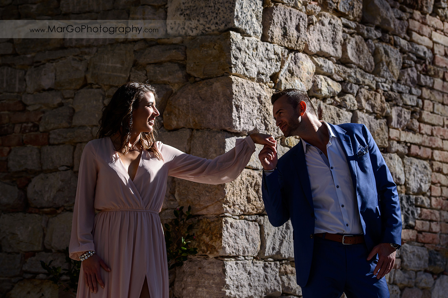 man in blue suit kissing hand of woman in pink dress on stone wall during Napa Valley engagement session at Castello di Amorosa in Calistoga