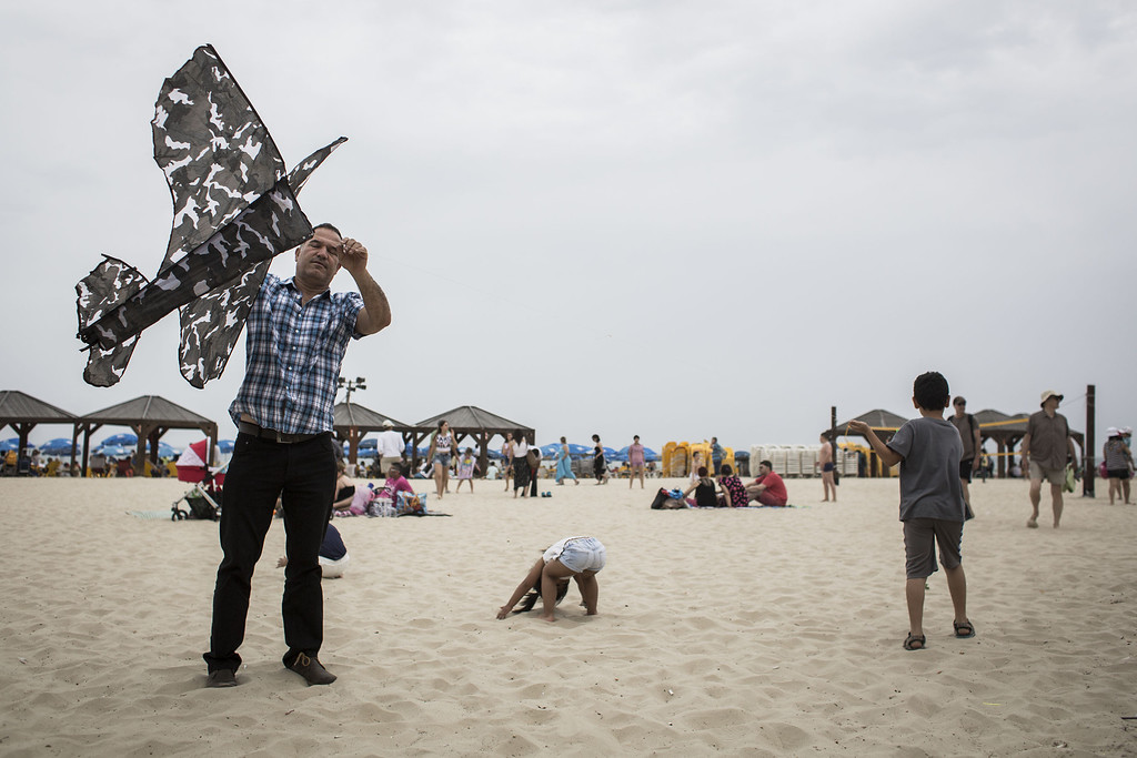 . An Israeli man flies a kite with his children on the beach in the Mediterranean sea as people wait for the military air show marking the 66th anniversary of Israel\'s independence to start on May 6, 2014 in Tel Aviv, Israel. The day marks when David Ben-Gurion, the Executive Head of the World Zionist Organization declared the establishment of a Jewish state in Eretz- Israel. (Photo by Ilia Yefimovich/Getty Images)