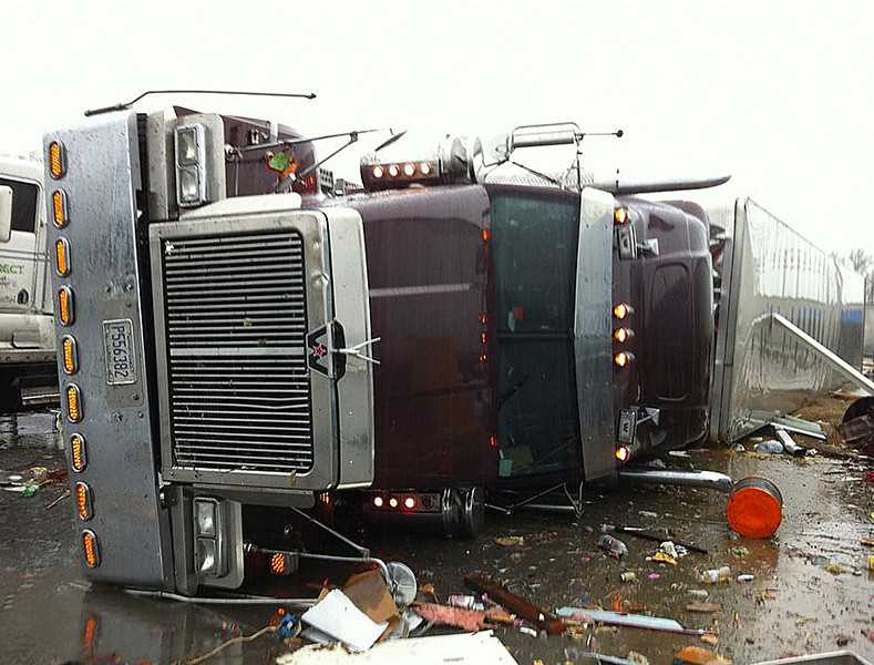 . In this image made from video and released by WSB TV in Atlanta, a tractor and trailer rest on the highway after a tornado moved through the town of Adairsville, Ga. on Wednesday, Jan 30, 2013. A fire chief says a storm that roared across northwest Georgia has left overturned vehicles on Interstate 75 northwest of Atlanta, and crews are responding to reports of people trapped in storm-damaged residential and commercial buildings. (AP Photo/WSB TV)