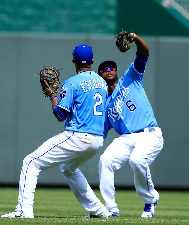 . Kansas City Royals center fielder Lorenzo Cain (6) and shortstop Alcides Escobar (2) during a baseball game against the Cleveland Indians at Kauffman Stadium in Kansas City, Mo., Sunday, Aug. 20, 2017. (AP Photo/Orlin Wagner)
