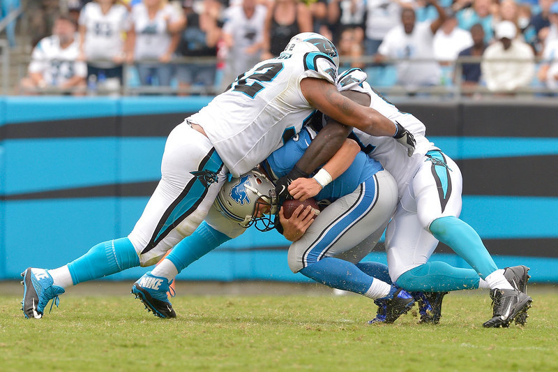 . Dwan Edwards #92 and Mario Addison #97 of the Carolina Panthers sack Matthew Stafford #9 of the Detroit Lions during their game at Bank of America Stadium on September 14, 2014 in Charlotte, North Carolina. The Panthers won 24-7.  (Photo by Grant Halverson/Getty Images)