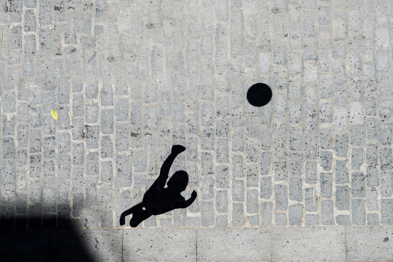The shadow of a kid kicking a soccer ball