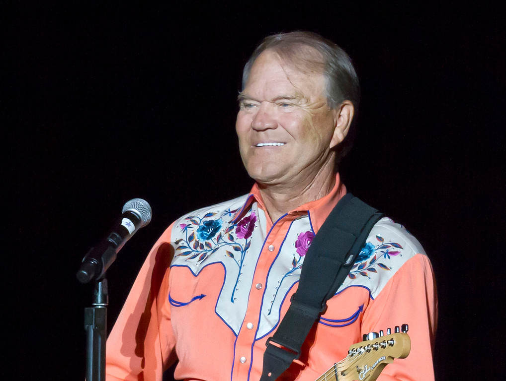 """. FILE - This Sept. 6, 2012 file photo shows singer Glen Campbell performing during his Goodbye Tour in Little Rock, Ark. Campbell, the grinning, high-pitched entertainer who had such hits as \""""Rhinestone Cowboy\"""" and spanned country, pop, television and movies, died Tuesday, Aug. 8, 2017. He was 81. Campbell announced in June 2011 that he had been diagnosed with Alzheimer\'s disease. (AP Photo/Danny Johnston, File)"""