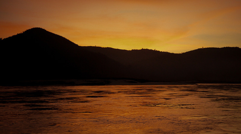 The sun slowly sets with a tangerine sunset over the Mekong River in Laos.