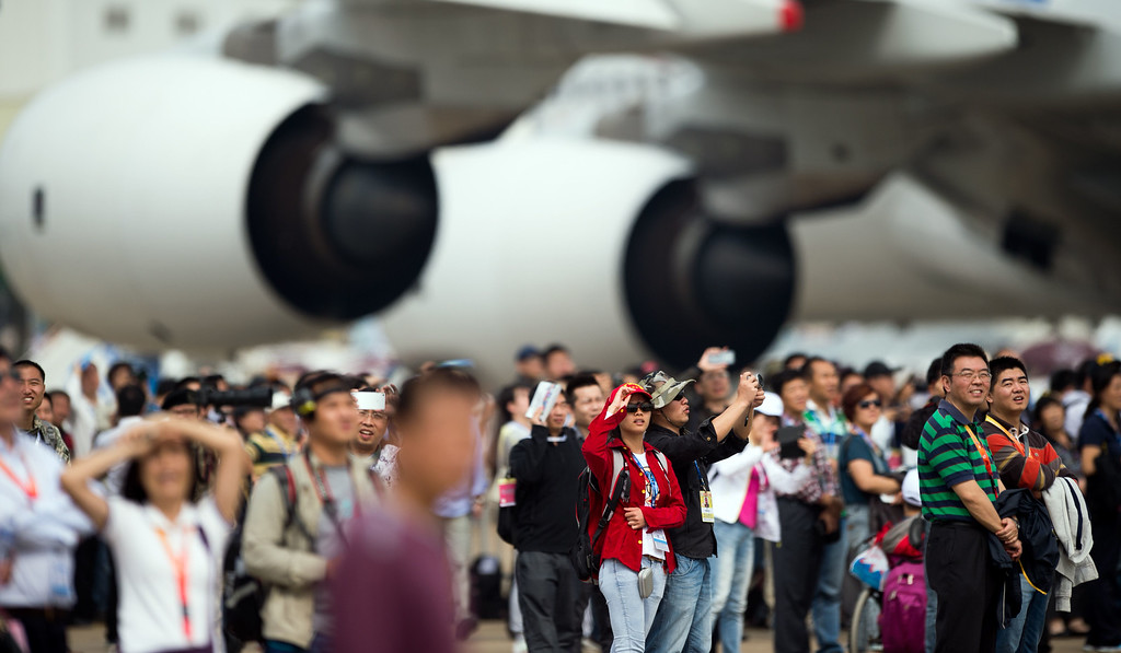 . People watch the J-10 fighter jets of the Bayi Aerobatic Team of PLA\'s (Peoples Liberation Army) Air Force perform next to an Airbus A380 jet at the Airshow China 2014 in Zhuhai, south China\'s Guangdong province on November 12, 2014.    AFP PHOTO / JOHANNES  EISELE/AFP/Getty Images