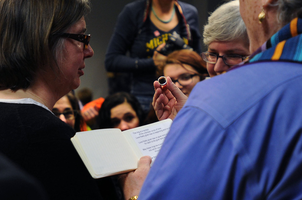 . Gail Gaisenhaner holds up a wedding ring as she officiates a marriage between Beth Sherman and Karen Hawver of Ann Arbor at the Washtenaw County Clerk\'s office in Ann Arbor, Mich., Saturday, March 22, 2014, the day after a federal court struck down Michigan\'s ban on gay marriage. The couple have been together for 20 years and have four children. (AP Photo/The Ann Arbor News, Brianne Bowen)