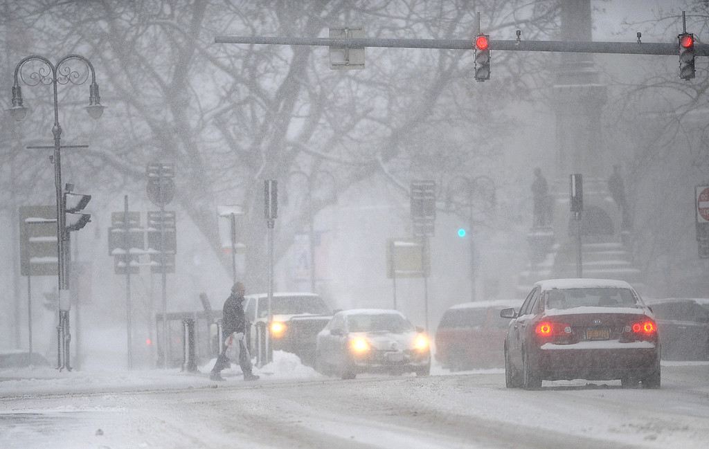 . In a Tuesday, Nov. 18, 2014 photo, a pedestrian crosses Public Square in Tuesday\'s snow and wind in Watertown, N.Y.  Watertown schools were closed Tuesday. A ferocious lake-effect storm left the Buffalo area buried under 6 feet of snow, trapping people on highways and in homes, and another storm expected to drop 2 to 3 feet more was on its way. (AP Photo/The Watertown Daily Times, Justin Sorensen)
