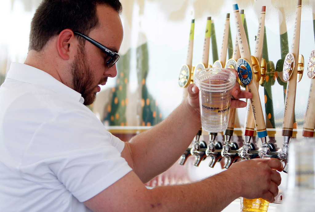 . Hangar 24 sales representative Andrew Peterson pours a selection of beer during the Hangar 24 AirFest and 6th Anniversary Celebration on Friday, May 16, 2014 at the Redlands Municipal Airport in Redlands, Ca. (Photo by Micah Escamilla/Redlands Daily Facts)