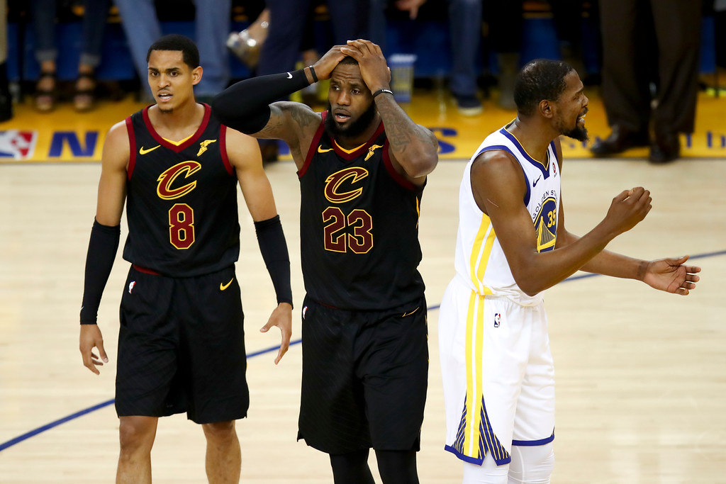 . Cleveland Cavaliers forward LeBron James (23) reacts between guard Jordan Clarkson (8) and Golden State Warriors forward Kevin Durant during the second half of Game 1 of basketball\'s NBA Finals in Oakland, Calif., Thursday, May 31, 2018. (AP Photo/Ben Margot)