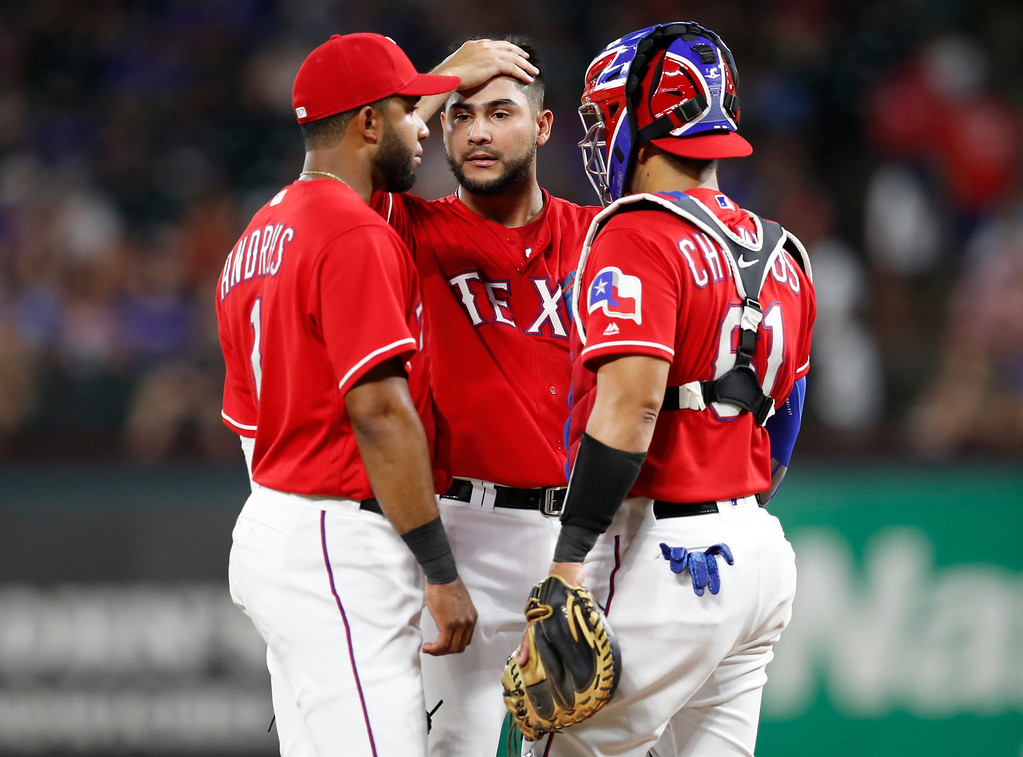 . Texas Rangers starting pitcher Martin Perez, middle, wipes his brow during a mound conference with shortstop Elvis Andrus (1) and catcher Robinson Chirinos (61) during the fifth inning of a baseball game against the Cleveland Indians, Friday, July 20, 2018, in Arlington, Texas. (AP Photo/Jim Cowsert)