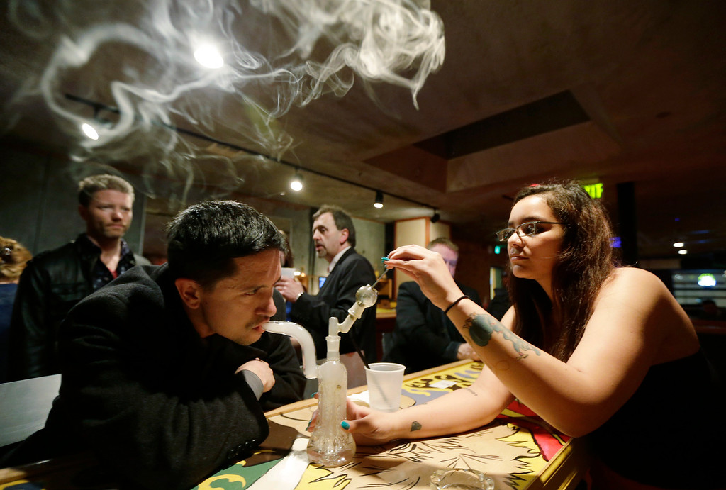 ". John Connelly, left, inhales marijuana vapor just after midnight Saturday, March 2, 2013, with the help of bar worker Jenae DeCampo, right, in the upstairs lounge area of Stonegate, a pizza-and-rum bar in Tacoma, Wash. Owner Jeff Call charges patrons a small fee to become a member of the private second-floor club, which prohibits smoking marijuana, but does permit ""vaporizing,\"" a method that involves heating the marijuana without burning it. Last fall, Washington and Colorado became the first states to legalize marijuana use for adults over 21. (AP Photo/Ted S. Warren)"