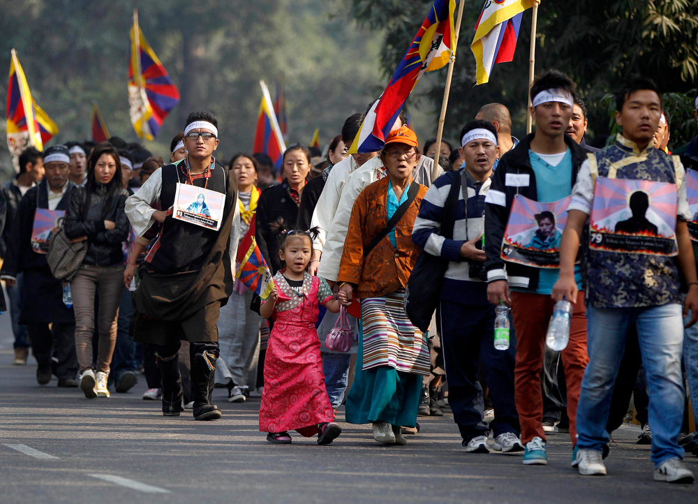 Description of . Exile Tibetans march wearing portraits of Tibetans who have allegedly immolated themselves in protest against Chinese rule, during a rally to mark World Human Rights Day in New Delhi, India, Monday, Dec. 10, 2012. At least 86 people have set themselves on fire since 2009. Tibetans also mark Dec. 10 as Nobel Peace Prize Day, the day the Dalai Lama received the Nobel peace prize in 1989. (AP Photo/Mustafa Quraishi)