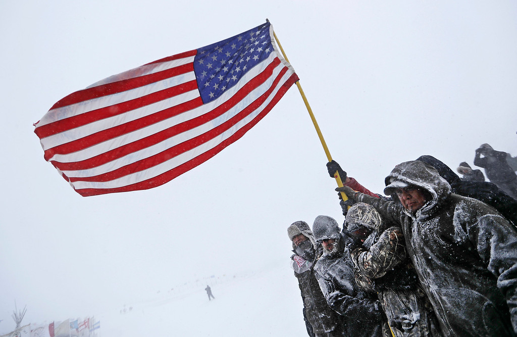 . Military veterans huddle together to hold an American flag against strong winds during a march to a closed bridge outside the Oceti Sakowin camp where people have gathered to protest the Dakota Access oil pipeline in Cannon Ball, N.D., Monday, Dec. 5, 2016. (AP Photo/David Goldman)
