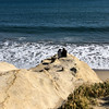 A couple sits on a rock formation on Seabright beach  in Santa Cruz