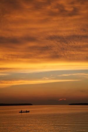 Evening Paddle, Blazing Sky. Canoe on Green Bay at twilight. Ephraim, Wisconsin.
