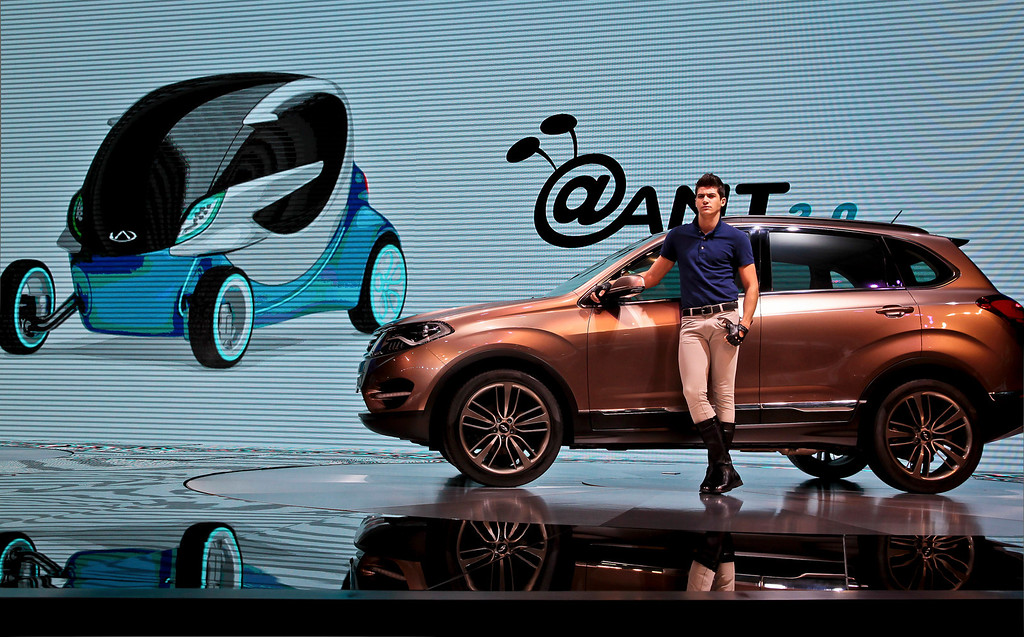 . A model poses with a Beta 5 SUV made by Chinese automaker Chery on display at the Shanghai International Automobile Industry Exhibition (AUTO Shanghai) media day in Shanghai Saturday, April 20, 2013. (AP Photo)
