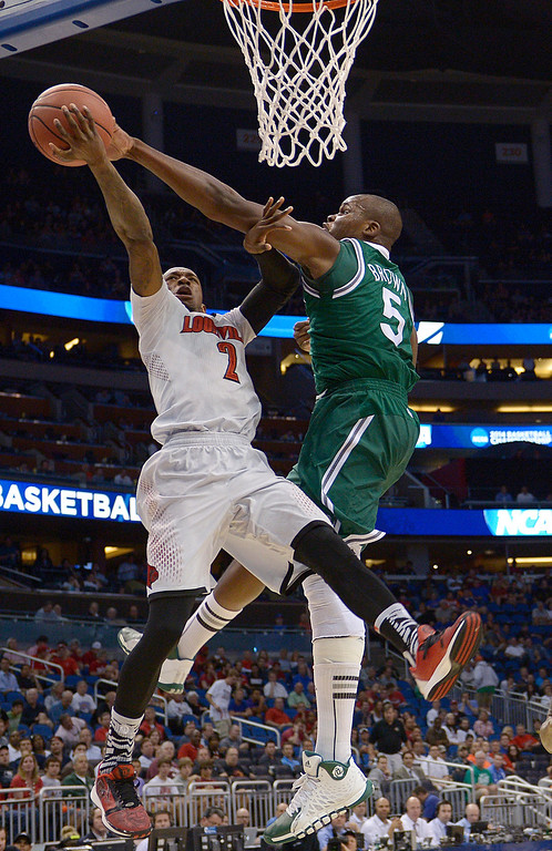 . Manhattan center Rhamel Brown (5) blocks a shot by Louisville guard Russ Smith (2) in a second-round game in the NCAA college basketball tournament Thursday, March 20, 2014, in Orlando, Fla.  (AP Photo/Phelan M. Ebenhack)