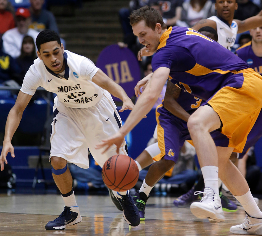 . Mount St. Mary\'s guard Julian Norfleet, left, and Albany forward Luke Devlin chase a loose ball in the first half of a first-round game of the NCAA college basketball tournament, Tuesday, March 18, 2014, in Dayton, Ohio. (AP Photo/Al Behrman)