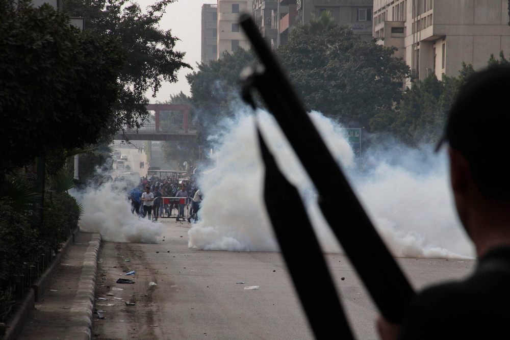 . Supporters of ousted President Mohammed Morsi look through tear gas by Egypt\'s security forces during clashes in Cairo, Egypt, Friday, Jan. 17, 2014. Morsi supporters held sporadic protests against this week\'s constitutional referendum as authorities said there was a deadly clash. (AP Photo/Aly Hazzaa)