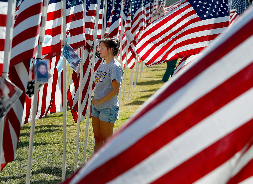 . Lucy Hundt, of Wisconsin, walks through rows of nearly 3,000 flags with the names of those who died in the attacks of Sept. 11, 2001, Tuesday, Sept. 11, 2018, at Tempe Beach Park in Tempe, Ariz.  (AP Photo/Matt York)