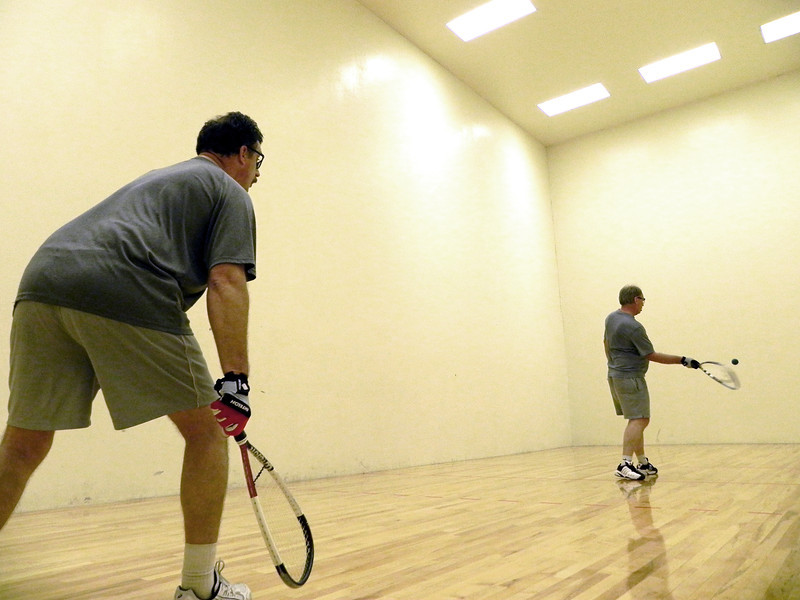2011/11/29 – On Tuesday nights I play in a racquetball league. I love the competition and the workout. After our two hours of play I got these two, Dave at the back and Val serving, to play while I tried to get a picture. it told them to make she they didn't hit me, not even trying to be funny.
