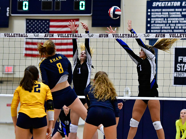 11/1/2018 Mike Orazzi | Staff Bristol Eastern's Ryley Plourde (11) and Zoe Lowe (7) and RHAM's Kaylin Hadley (8) during the CCC Volleyball Tournament at Avon High School Thursday night.