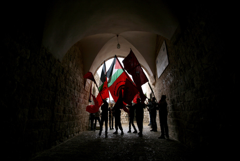 Description of . Palestinian demonstrators wave their national flag (C) and the red party flag of the Democratic Front for the Liberation of Palestine (DFLP) under a covered passage during a protest in support with Palestinian prisoners on hunger strike in Israeli jails and against administrative detention in the northern West Bank village of Araba, near Jenin, on February 1, 2013. SAIF DAHLAH/AFP/Getty Images
