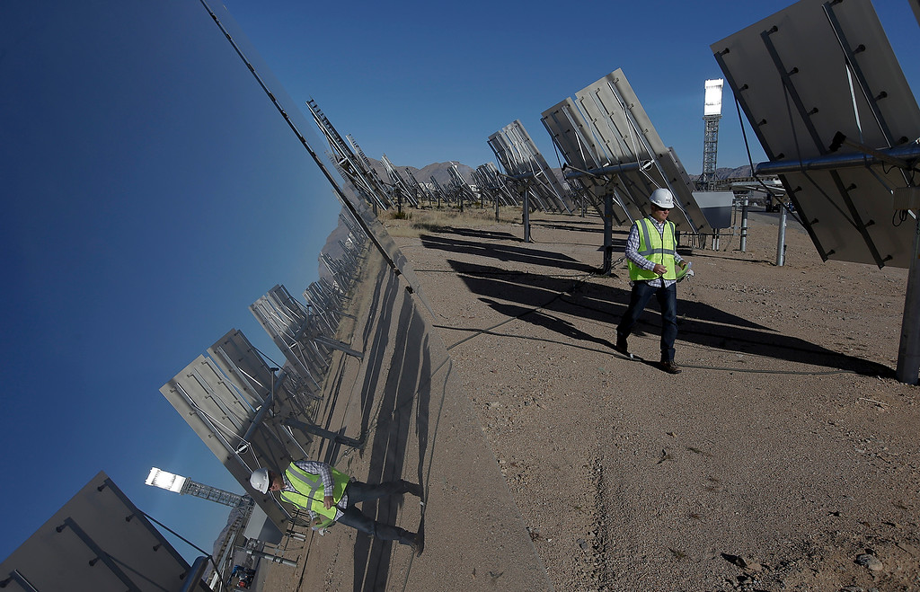 . Jeff Holland walks near some of 300,000 computer-controlled mirrors that reflect sunlight to boilers that sit on 459-foot towers Tuesday, Feb. 11, 2014 in Primm, Nev.  (AP Photo/Chris Carlson)