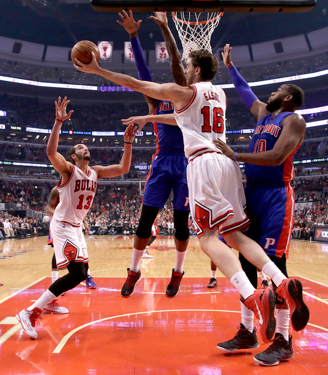 . Chicago Bulls forward Pau Gasol (16) looks to pass the ball to center Joakim Noah (13), past the arms of Detroit Pistons forward Josh Smith and forward Greg Monroe (10), during the first half of an NBA basketball game Monday, Nov. 10, 2014, in Chicago. (AP Photo/Charles Rex Arbogast)