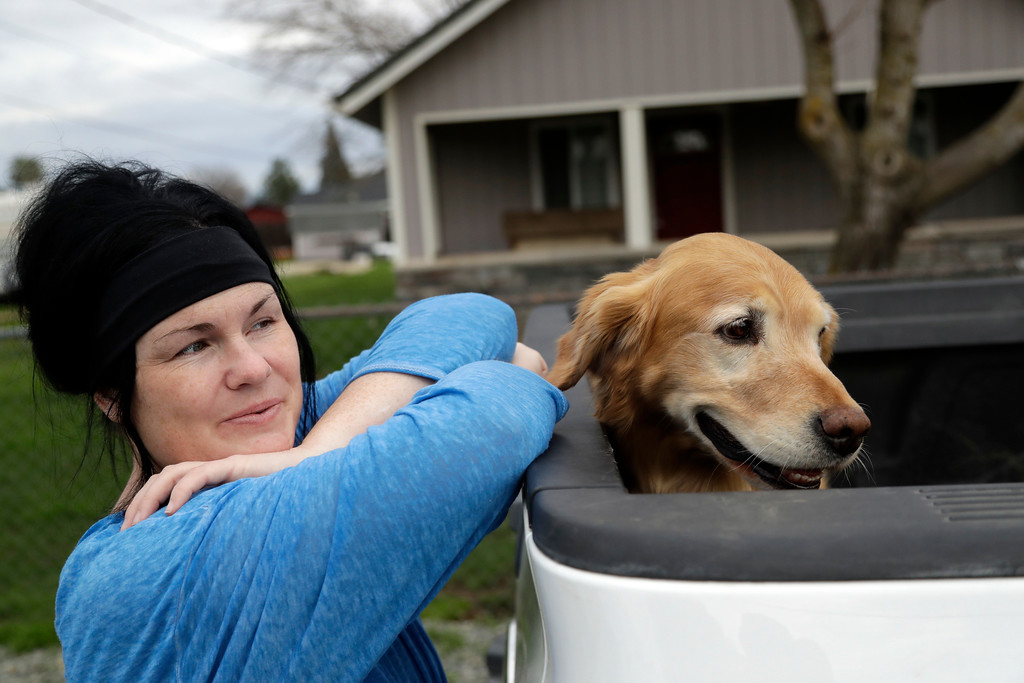 . Leanne Fowler, left, rests on the bed of a pick up truck next to family dog Riley after returning home from evacuation Wednesday, Feb. 15, 2017, in Oroville, Calif. Authorities say the immediate danger has passed and allowed people living downstream of the Oroville Dam to go back home Tuesday after ordering an evacuation Sunday. But, new storms forecast to hit Northern California this week will test quick repairs to the dam.  (AP Photo/Marcio Jose Sanchez)