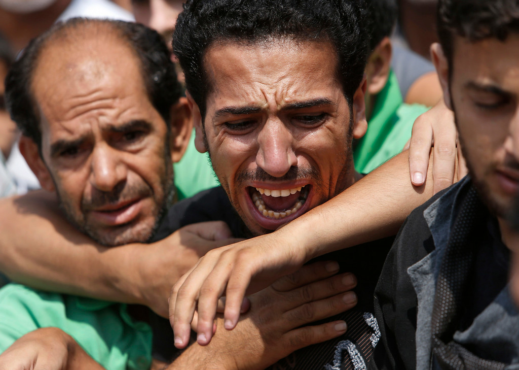 . A relative bursts into tears as mourners try to comfort him as they gather around the bodies of seven members of the Kelani family, killed overnight by an Israeli strike in Gaza City, during their funeral in Beit Lahiya, northern Gaza Strip, on Tuesday, July 22, 2014. Ibrahim Kelani, 53, his wife Taghreed and their five children, were killed in the strike on a Gaza City high rise. Ibrahim\'s brother Saleh Kelani said Tuesday that his brother and his brotherís children, ranging in age from four to 12, had German citizenship, while his wife had not. The family had rented the apartment in the high-rise after fleeing their home in the northern Gaza town of Beit Lahiya which came under heavy shelling by the Israeli army. (AP Photo/Lefteris Pitarakis)