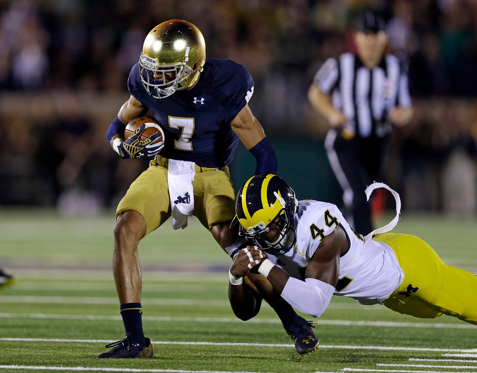 . Notre Dame wide receiver William Fuller, left, is tackled by Michigan defensive back Delano Hill during the second half of an NCAA college football game in South Bend, Ind., Saturday, Sept. 6, 2014. (AP Photo/Michael Conroy)