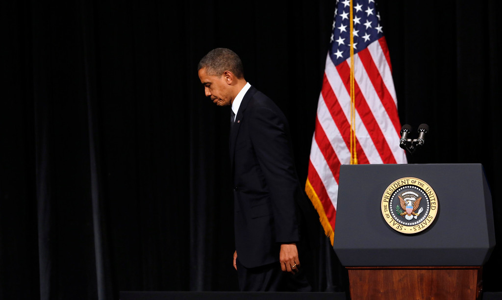 . U.S. President Barack Obama looks down as he walks from the rostrum after speaking at a vigil held at Newtown High School for families of victims of the Sandy Hook Elementary School shooting in Newtown, Connecticut December 16, 2012. Obama is visiting Newtown High School to meet with the families of the victims and to thank first responders to the school shooting here that was one of the deadliest such incidents in the nation\'s history. REUTERS/Kevin Lamarque