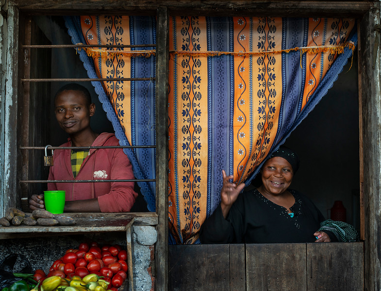 Mother and son  with their little vegetable stall outside their home, in a small village close to Lushoto.  Tanzania, 2019.