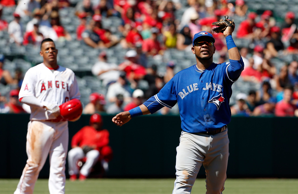 . Toronto Blue Jays first baseman Edwin Encarnacion waves his glove at a swarm of bees in the third inning of a baseball game against the Los Angeles Angels in Anaheim, Calif., Sunday, Sept. 18, 2016. (AP Photo/Christine Cotter)